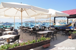 Bar and tables on the Marsaxlokk Bay promenade