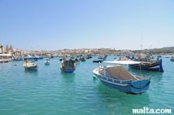 Boats and luzzu in the blue water of Marsaxlokk harbour