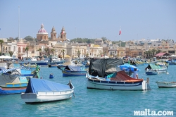 Luzzu in the harbour of Marsaxlokk and the parish church in the background
