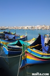 Traditional Maltese luzzu onshore of the Marsaxlokk Bay