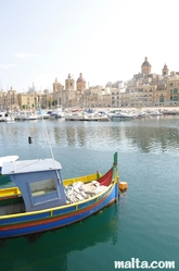 Senglea harbour with a luzzu and the Marine Museum of Victoriosa in the background
